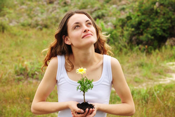 a woman holds a flower and looks up at sky