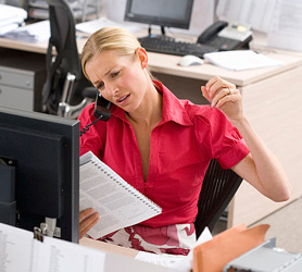 Stressed-out woman talks on phone at office desk