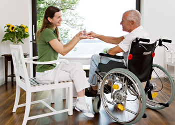 a patient advocate gives medicine to her elderly client, who is in a wheelchair